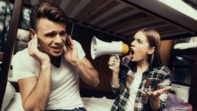 Woman screaming to mouthpiece on man covering ears. Hostel for Young People. Best Friends Traveling. Small Room in Hostel. spend time Together. bunk beds in room royalty free stock photography