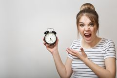The woman is screaming. Woman holding an alarm clock stock images