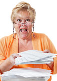 Woman screams over heathcare paperwork. Mature woman screams in frustration over a huge stack of insurance forms and healthcare paperwork Royalty Free Stock Photography