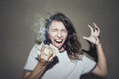 Woman screams and swears with a lit crumpled piece of paper in a. Nger and frustration Stock Images
