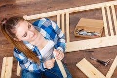 Woman with screwdriver nails assembling furniture. Stock Photos