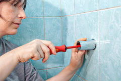 Woman with screwdriver, tighten bracket for shower to wall. Replacing the plumbing in the bathroom, the woman fixed to the wall holder bracket for a shower royalty free stock photo