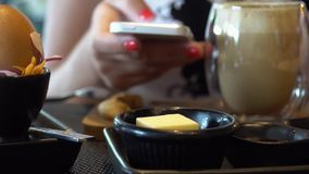 Woman Scrolling Mobile Phone at Breakfast. Shot with a Sony a6300 fps29,97 4k stock footage