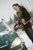 Woman scrubbing car in winter Royalty Free Stock Photo