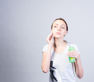 Woman Scrubbing Face Using Cotton with Cleanser. Half Body Shot of a Young Woman Scrubbing her Cheek Using Cotton with Facial Cleanser While Holding a Bottle and Royalty Free Stock Photo