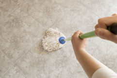 Woman scrubbing floor with a mop Royalty Free Stock Photography
