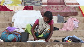 Woman scrubbing laundry on the ghats of the Ganges river in India. VARANASI, INDIA - 25 FEBRUARY 2015: Woman scrubbing laundry on the ghats of the Ganges river stock footage