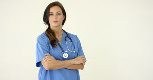 Woman in scrubs crosses arms and smiles at camera Stock Images