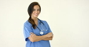 Woman in scrubs crosses arms and smiles at camera Royalty Free Stock Photo