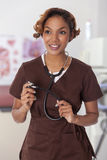 Woman in scrubs holds a stethoscope. Pretty young medical professional smiles with a stethoscope Stock Photos