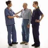Woman in scrubs shaking hands Royalty Free Stock Image