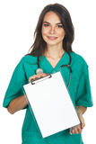 Woman is scrubs showing a blank clipboard sign Stock Image