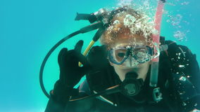 Woman in scuba gear looking at camera underwater making ok sign stock video
