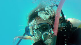 Woman in scuba gear looking at camera underwater stock footage