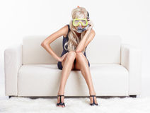 Woman in scuba mask. Young blond woman in scuba mask on couch with white furs on floor royalty free stock image