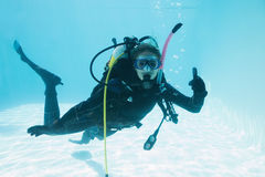 Woman on scuba training submerged in swimming pool showing thumbs up Stock Images