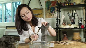 Woman sculpts from raw clay the flower vase stock video