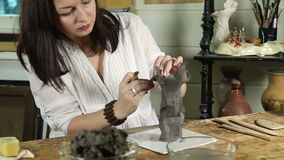 Woman sculpts from raw clay stock footage