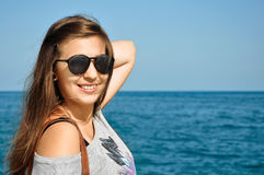 Woman and the sea. Pretty young female with sunglasses on at the beach Stock Photos