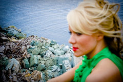 Woman at sea. Portrait of a pretty blond woman at a rocky sea shore. The focus is on the background Royalty Free Stock Photo