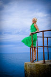 Woman at sea. A young woman in green dress posing at windy sea (ocean Stock Photography