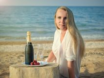 Woman by the sea with a bottle of sparkling wine and strawberries. A full bottle of shaman`s, strawberries and the woman on the beach. The concept of a happy stock photo