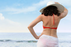 The woman on sea coast in a hat Stock Photos