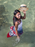 Woman in the sea greeting with straw hat Stock Image