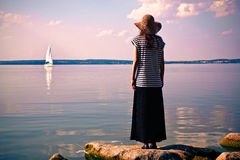Woman at sea looking at ship Stock Image