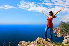 Woman sea and mountain. Young happy woman standing on the rock near the sea Royalty Free Stock Photo