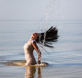 Woman in the sea splashing water Royalty Free Stock Image