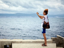 Woman at the sea taking photos Stock Images