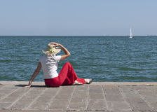 Woman by sea watches yacht in sunshine Stock Photo