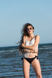Woman in sea water wear bikini, sunglasses and white shirt Stock Images