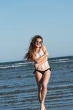 Woman in sea water wear bikini, sunglasses and white shirt Stock Photography