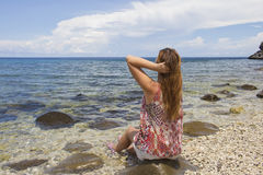 The woman and the sea. Young red hair woman sitting by the sea on the beach. S. Taring at sea picture. Meditation by sea image. Ecotourism illustration: clear Stock Photos