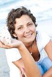 Woman on seacoast with a cockleshell Stock Photography