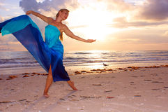 A woman and a seagull. An attractive adult woman is dancing on the beach with the sun behind her and a seagull in the background, she appears to be carefree and Royalty Free Stock Photography