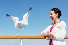 Woman and seagull on deck of ship. Laughing woman and seagull on deck of ship Royalty Free Stock Photos