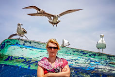 Woman and seagulls in a port Royalty Free Stock Image