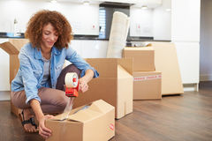 Woman Sealing Boxes Ready For House Move. In Kitchen stock images