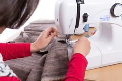 Woman seamstress thread inserts in the sewing machine. Stock Photography
