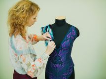 Woman seamstress working in his Studio. The mannequin is wearing a lace bodysuit. royalty free stock image