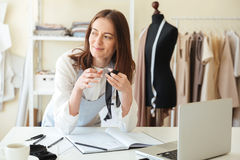 Woman seamstress working with laptop and fabrics Royalty Free Stock Photos