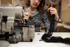 Woman seamstresses works with black lace in the workchop. Woman seamstresses works with black lace on sewing machines in the workshop Royalty Free Stock Photography