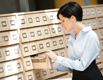 Woman searches something in card catalog. Woman seeks something in card catalog composed of set of wood boxes at the library. Education and research Stock Photos