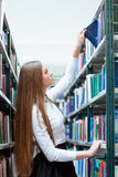 Woman searching book in university library Royalty Free Stock Photography