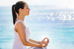 Woman searching for inner self at yoga session. Close up side side view portrait of young woman in casual wear searching for spiritual enlightenment next to sea royalty free stock photo