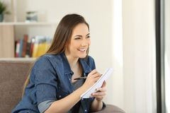 Woman searching inspiration to write in a notebook. Sitting in a couch in the living room at home Royalty Free Stock Images