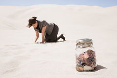 Woman searching for jar of coins in desert Stock Photo